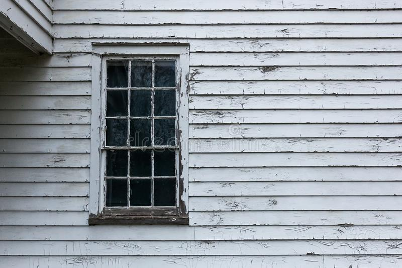 Old Glass Windows. An old glass window is surround by peeling paint and in need of repair stock image