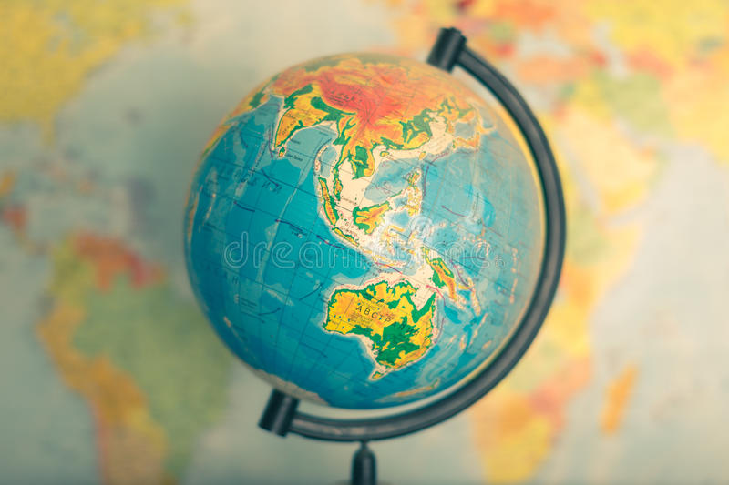 Old globe on world map background. Globe on a blurred background of the political map of the world stock image