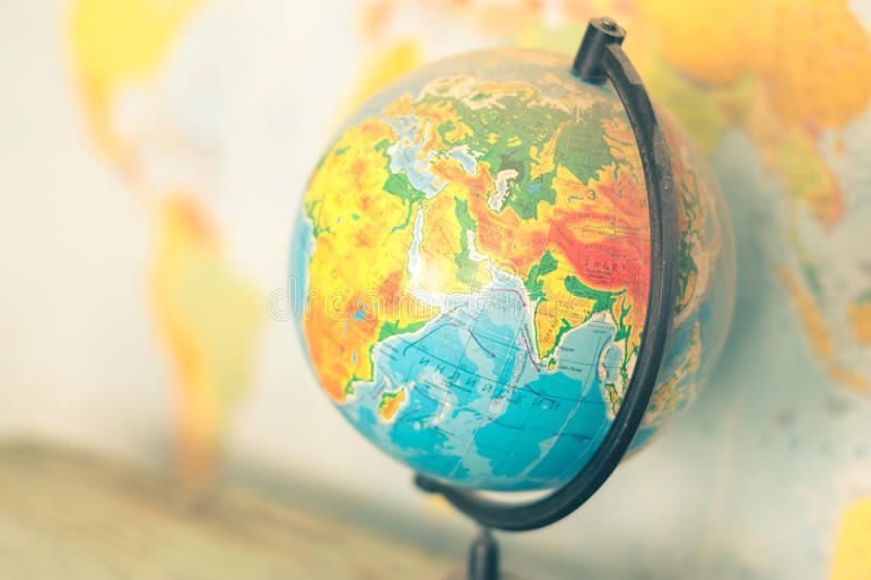 Old globe on world map background. Globe on a blurred background of the political map of the world stock photography