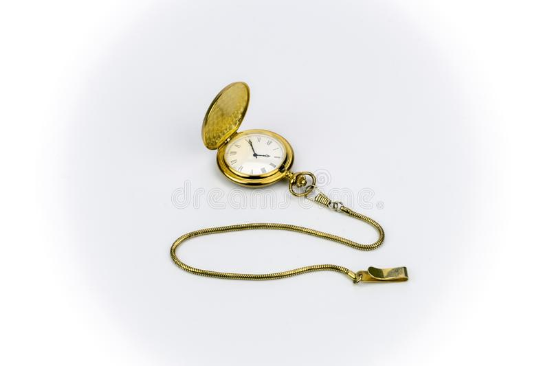Old gold Pocket Watch. View of a gold pocket watch with gold chain on a plain background royalty free stock photo
