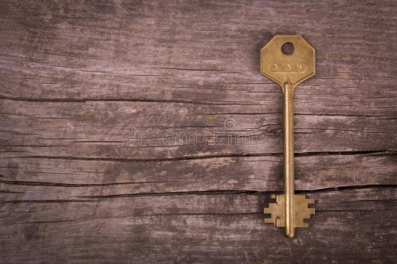 Old golden key. On a old wooden table stock photo