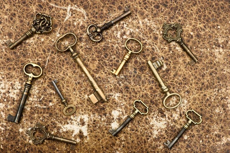 Old golden keys over vintage paper background stock photo
