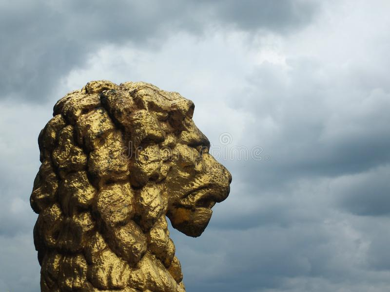 Old golden lion statue in profile decorating the historic rochdale town hall against a dramatic sky. An old golden lion statue in profile decorating the historic stock photo