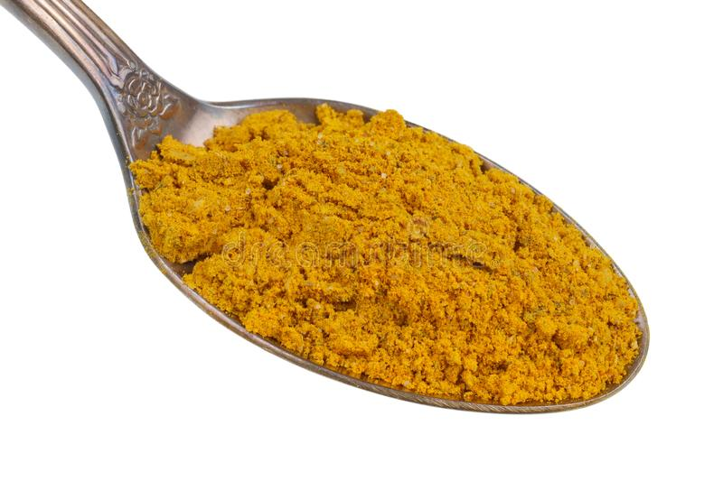 In the old golden spoon there is a small pile of food - ground Indian curry spice isolated macro. In the old golden spoon there is a small pile of food - ground royalty free stock photo