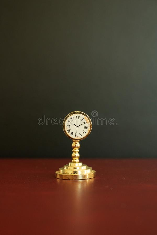 An old golden vintage miniature clock or watch royalty free stock photography
