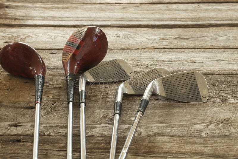 Old golf clubs on rough wood surface royalty free stock photo