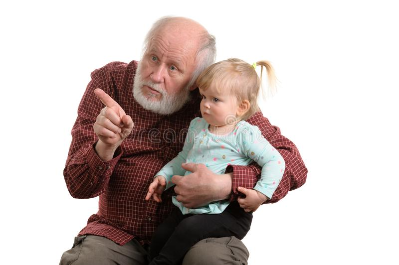 Old good grandpa and his little granddaughter. Little granddaughter sitting at lap of her grandpa, isolated stock images