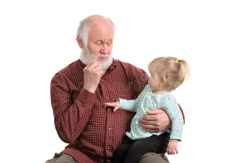 Old good grandpa and his little granddaughter. Little granddaughter sitting at lap of her grandpa, isolated royalty free stock photography