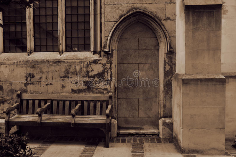Old gothic church door bricked up and the bench nearby royalty free stock images