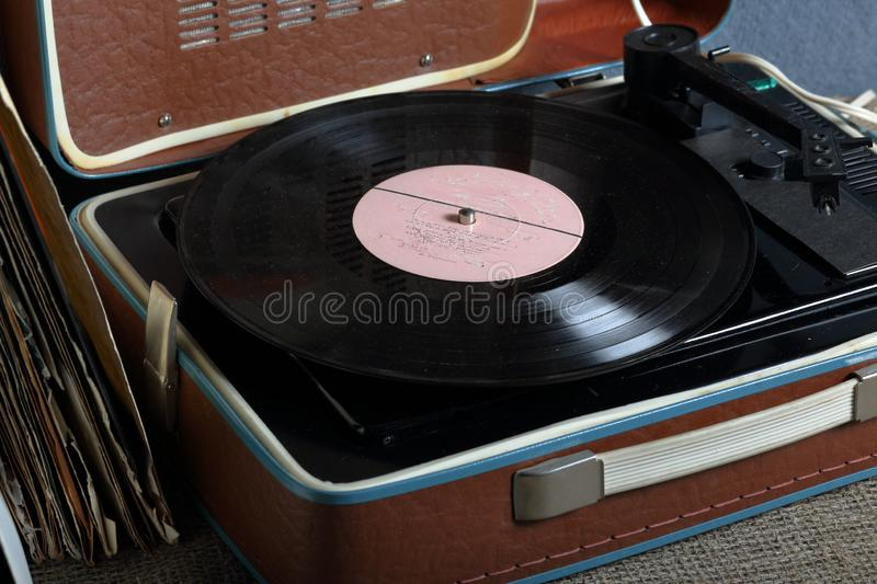 An old gramophone with a vinyl record mounted on it. stock image
