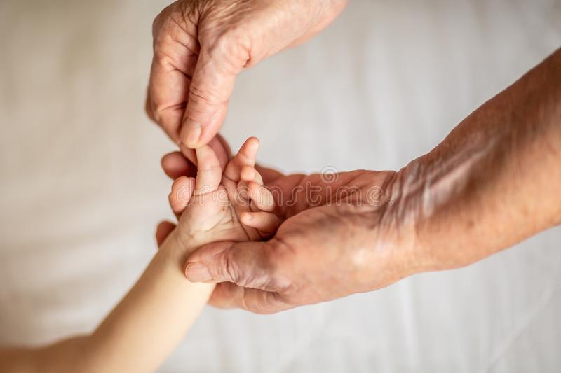 Old grandmother hands holding newborn hand, fourth generation family life. the concept of a family and a new life into a selective stock photo