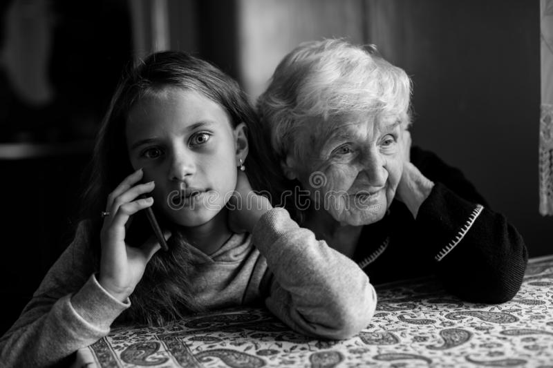 Old grandmother listens as the granddaughter of a little girl talking on a mobile phone. Black and white photo royalty free stock photography