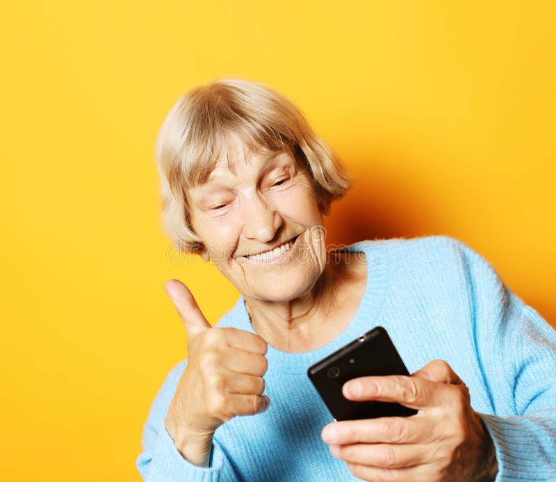 Old grandmother is talking to her grandchildren by phone, smiling and greeting them. Lifestyle, family  and people concept: old grandmother is talking to her royalty free stock images