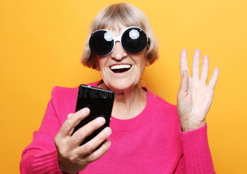 Old grandmother is talking to her grandchildren by phone, smiling and greeting them. Lifestyle, family  and people concept: old grandmother is talking to her royalty free stock photography