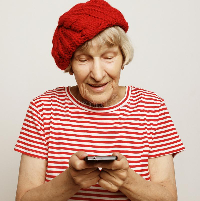 Old grandmother is talking to her grandchildren by phone, smiling and greeting them. Lifestyle, family  and people concept: old grandmother is talking to her stock photos