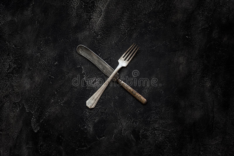 Old grange knife and fork X on concrete top view. Old grange knife and fork X on concrete stock photo