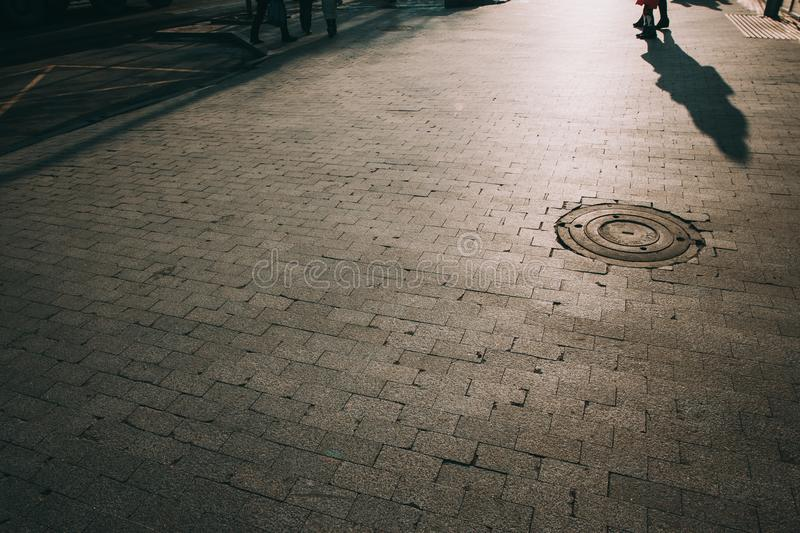 Old granite cobbles with sewer hatches. With sun light stock images