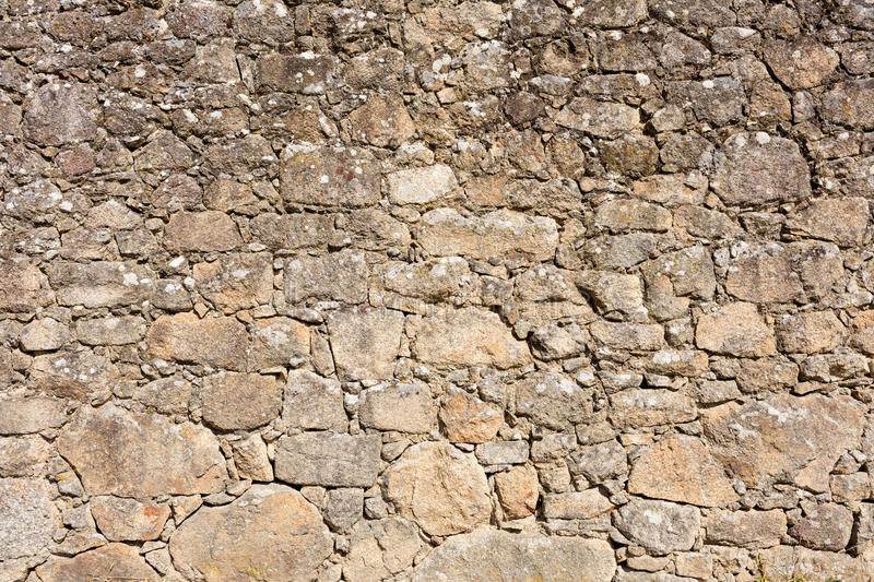 Old granite stone wall. Old stone wall made with irregular granite pieces stock photography