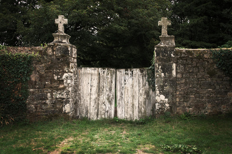 Old Graveyard Gate. Old wooden and weathered Gate of a Graveyard surrounded by a massive stone wall overgrown with Ivy. The posts of the gate have stone crosses royalty free stock photography