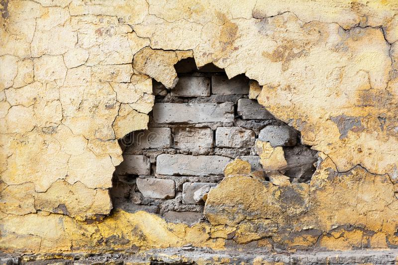 An old gray brick wall with cracks and a crumbling fragment of yellow stucco. Background texture for repair and restoration. conce. Pt of deception and broken stock photos