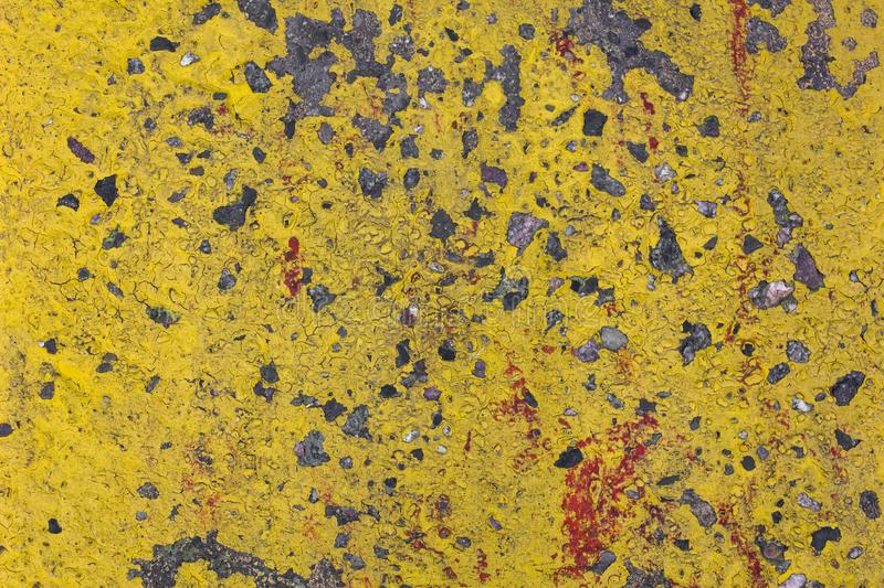 Old gray concrete wall with protruding stones and peeling bright yellow paint. rough surface texture royalty free stock image