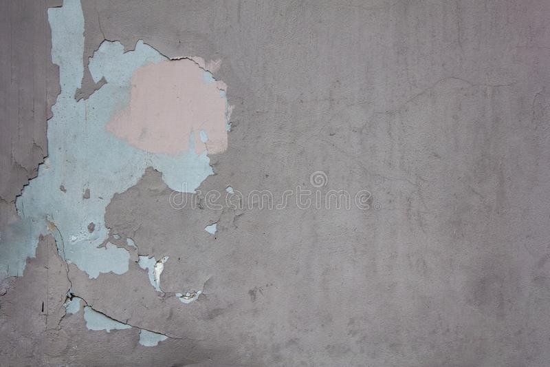 Old gray damaged wall with cracks and spots of peeling blue and pink paint. rough surface texture. A old gray damaged wall with cracks and spots of peeling blue stock images