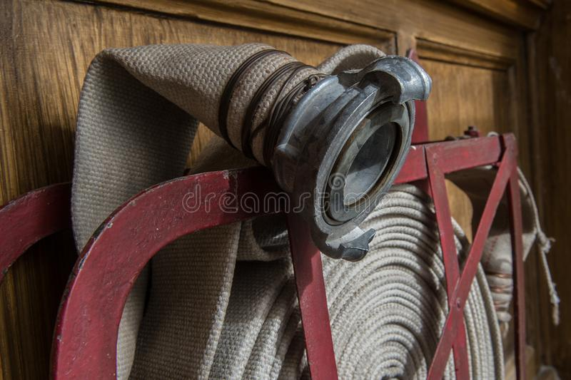 Twisted fire hose on fire shield. An old gray fire hose made of fireproof material attached to a special stand on a wooden wall. Connecting pipes made of metal royalty free stock photography