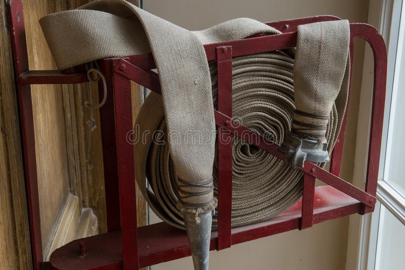 Twisted fire hose on fire shield. An old gray fire hose made of fireproof material attached to a special stand on a wooden wall. Connecting pipes made of metal royalty free stock image