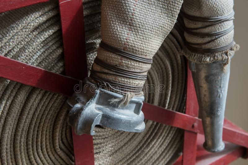 Twisted fire hose on fire shield. An old gray fire hose made of fireproof material attached to a special stand on a wooden wall. Connecting pipes made of metal royalty free stock photo