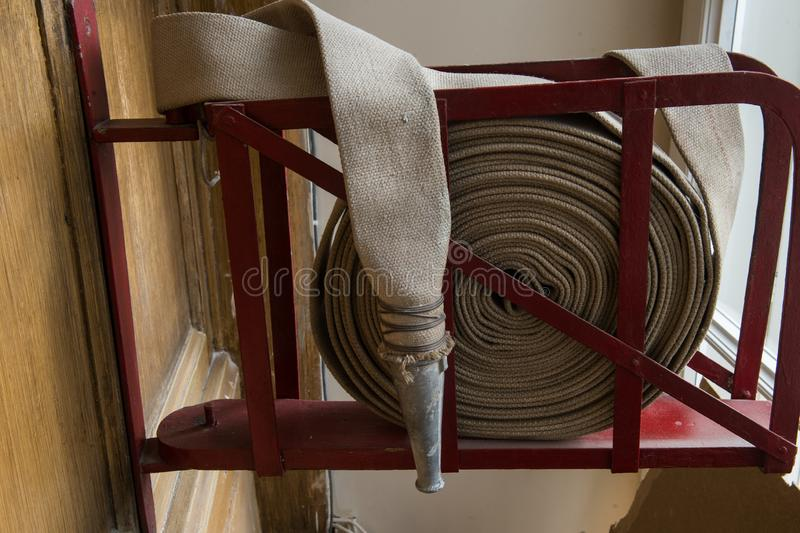 Twisted fire hose on fire shield. An old gray fire hose made of fireproof material attached to a special stand on a wooden wall. Connecting pipes made of metal stock image