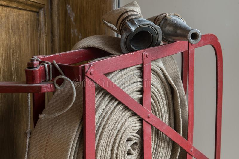 Twisted fire hose on fire shield. An old gray fire hose made of fireproof material attached to a special stand on a wooden wall. Connecting pipes made of metal stock photo