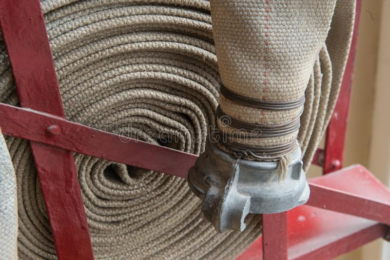 Twisted fire hose on fire shield. An old gray fire hose made of fireproof material attached to a special stand on a wooden wall. Connecting pipes made of metal royalty free stock photos