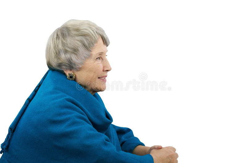 Old gray-haired woman in blue poncho. Sits in profile stock photos