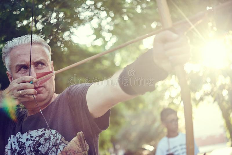 Old gray man shooting from a classic wooden English bow stock photos