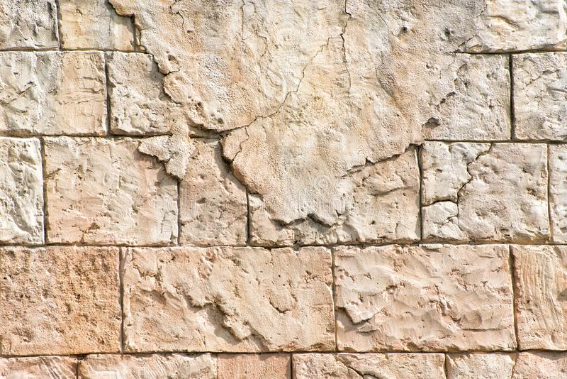 Old gray wall of rectangular stone blocks with remnants of plaster. Abstract background royalty free stock photography
