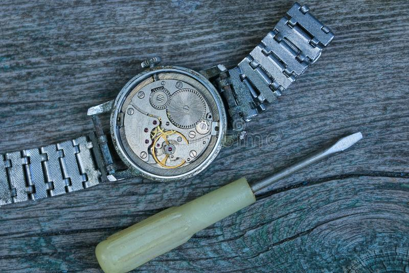 Old gray watch with an open mechanism and a metal strap with a screwdriver stock images