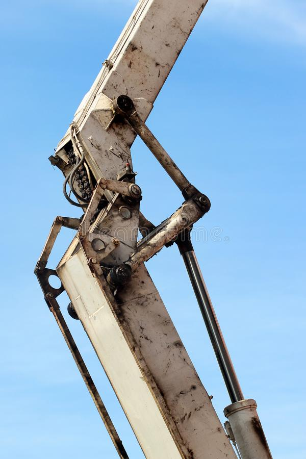 Old greasy and dirty hydraulic piston of white backhoe against blue sky. Heavy machine for excavation in construction site. royalty free stock images