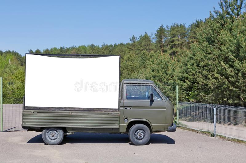 An old green army truck with a billboard set in a forest recreation area. An old no name green army truck with a empty  billboard set in a pine  forest stock photography