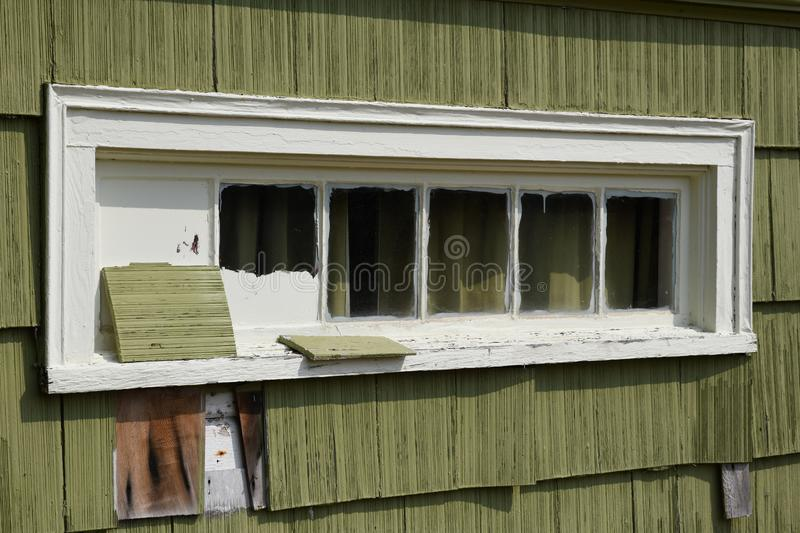Old green building with white window stock photography