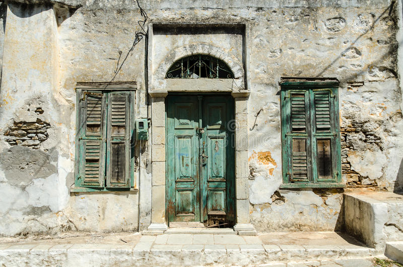 Old green door and windows of the house. Old green door and windows of the collapsed house stock image