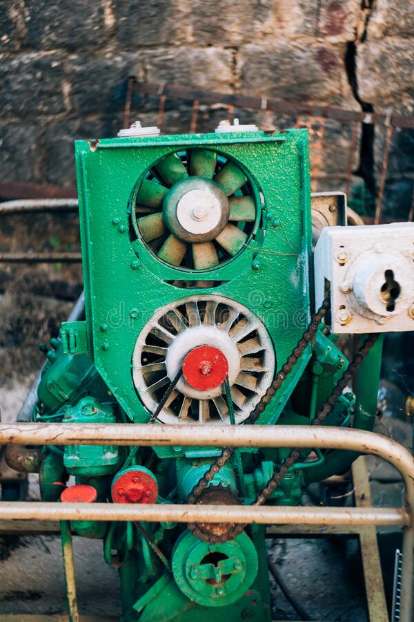 Old green internal combustion engine against the background of a stone wall. Home-made system, internal combustion engine painted in a purposeful color royalty free stock image
