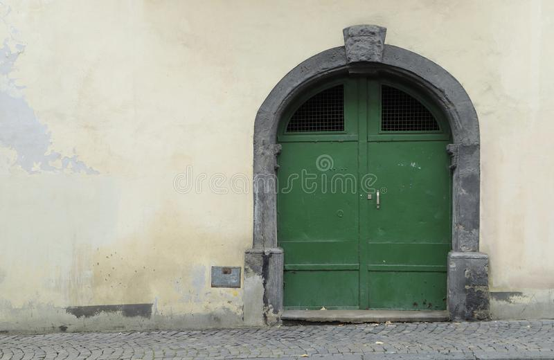 Old green iron door in a shabby weathered wall. royalty free stock photos