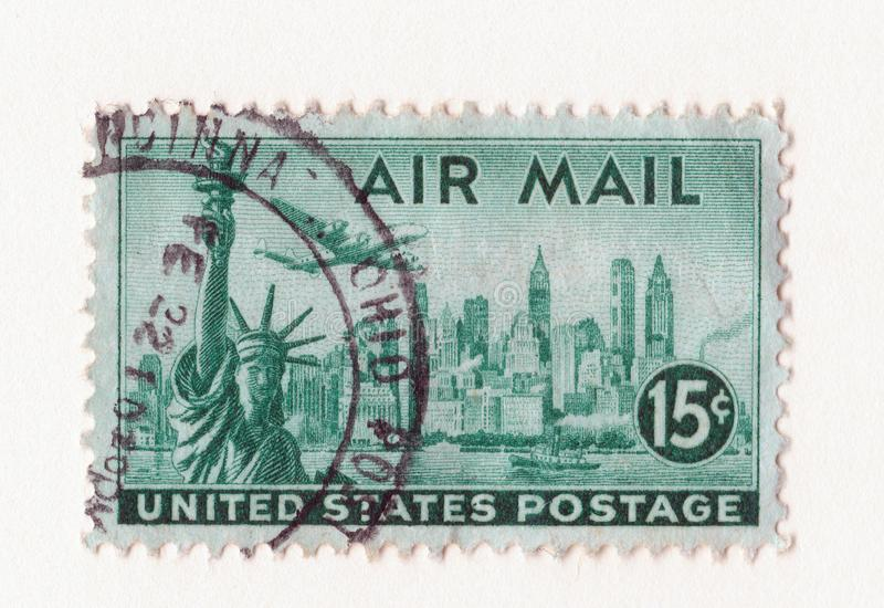 Old green vintage american air mail postage stamp with the statue of liberty Manhattan and an aircraft royalty free stock photography