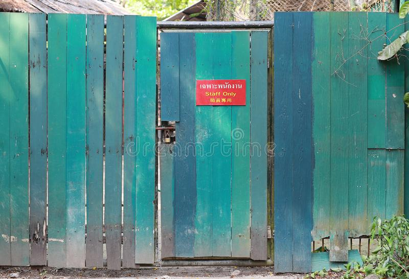 Old green wooden fence and locked door with text `Staff Only` on red label royalty free stock images