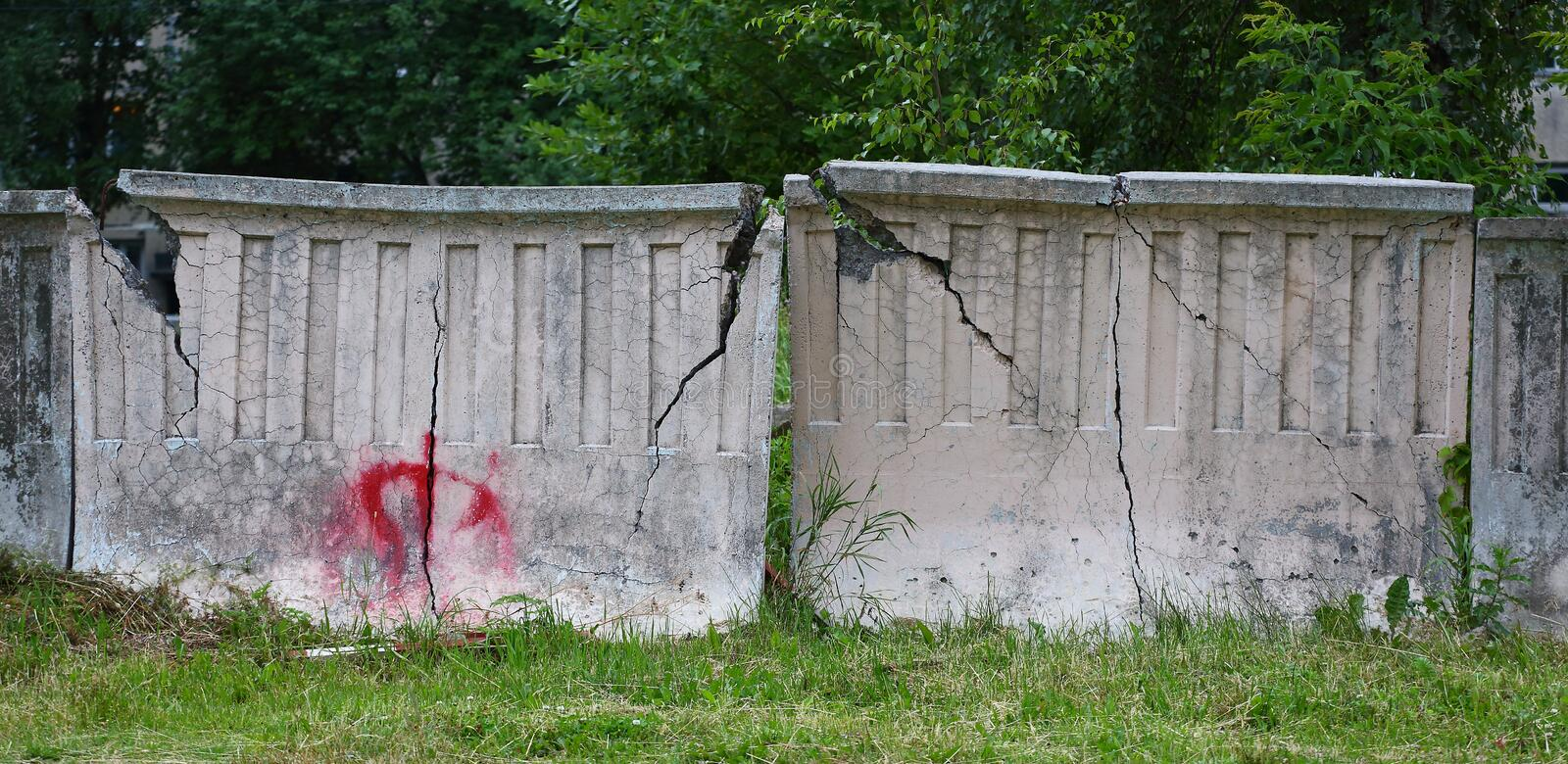 Old grey concrete cracked fence on green grass. The old grey concrete cracked fence on green grass stock photo