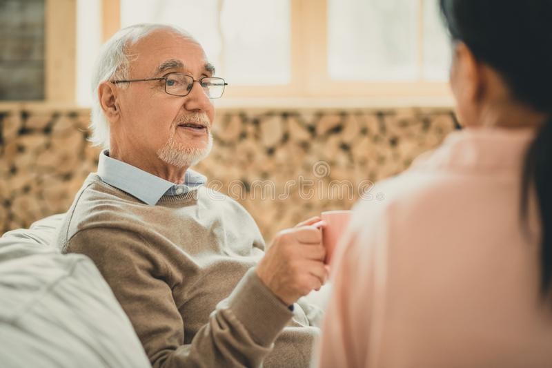 Old grey-haired man having pleasant time with his female friend. Cups of drinks. Old grey-haired men having pleasant time with his female friend during rest in stock image