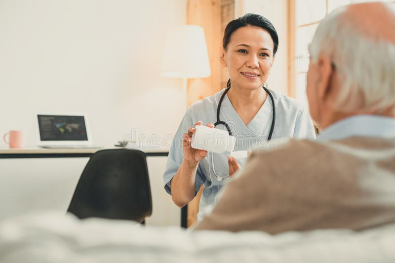 Old grey-haired man and his nurse sitting in consulting room. Patient during appointment. Old grey-haired men and his nurse sitting in consulting room discussing royalty free stock photography