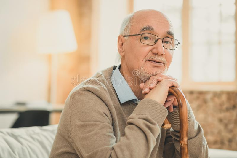 Old grey-haired man wisely looking while sitting on the sofa. Thoughtfully relying on. Old grey-haired man wisely looking while sitting on the sofa in clear stock photography