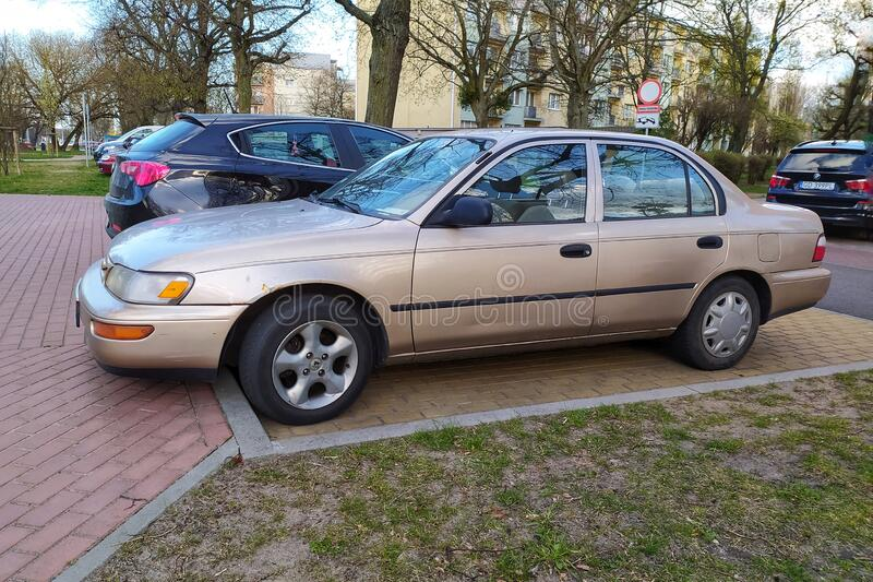 Old grey Toyota Corolla sedan four doors parked. Old grey Japanese Toyota Corolla sedan car parked. Four doors version, Front and left side view. This very stock photos
