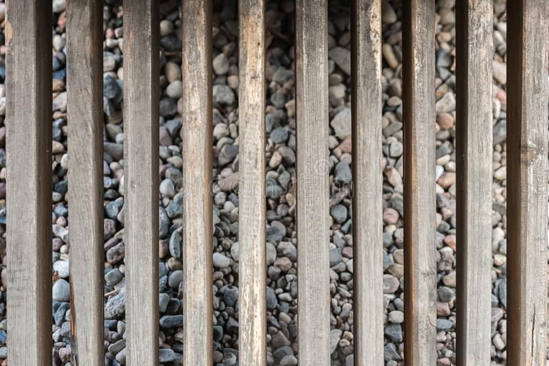 Old grey vertical fence and small river stones background. Vintage wood texture pattern stock photography